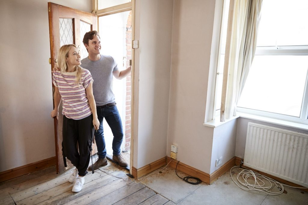 Man and woman entering an empty house for sale