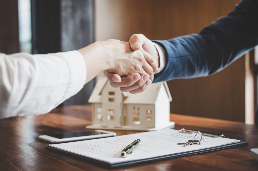 Man and woman shaking hands for real estate house deal