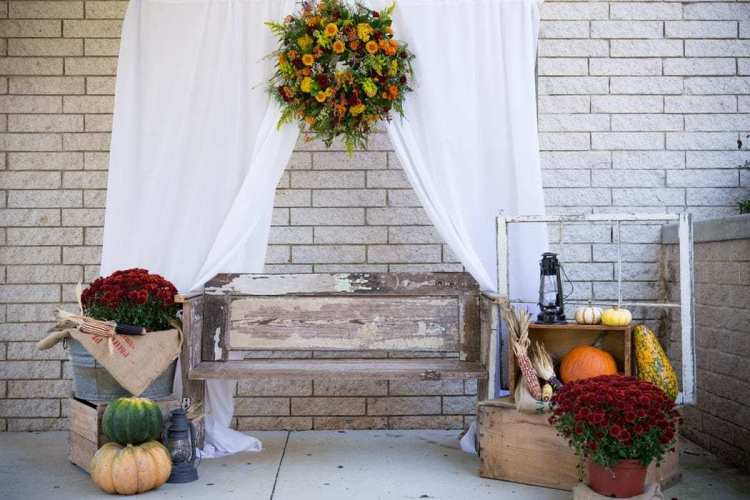 Fall decor including a wreath, potted plants, and gourds, all placed around a small bench.