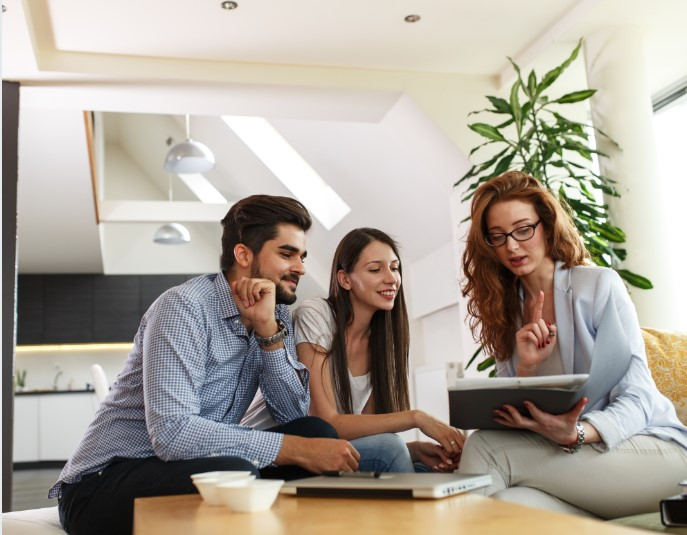 A real estate agent helps a young couple with a home transaction.