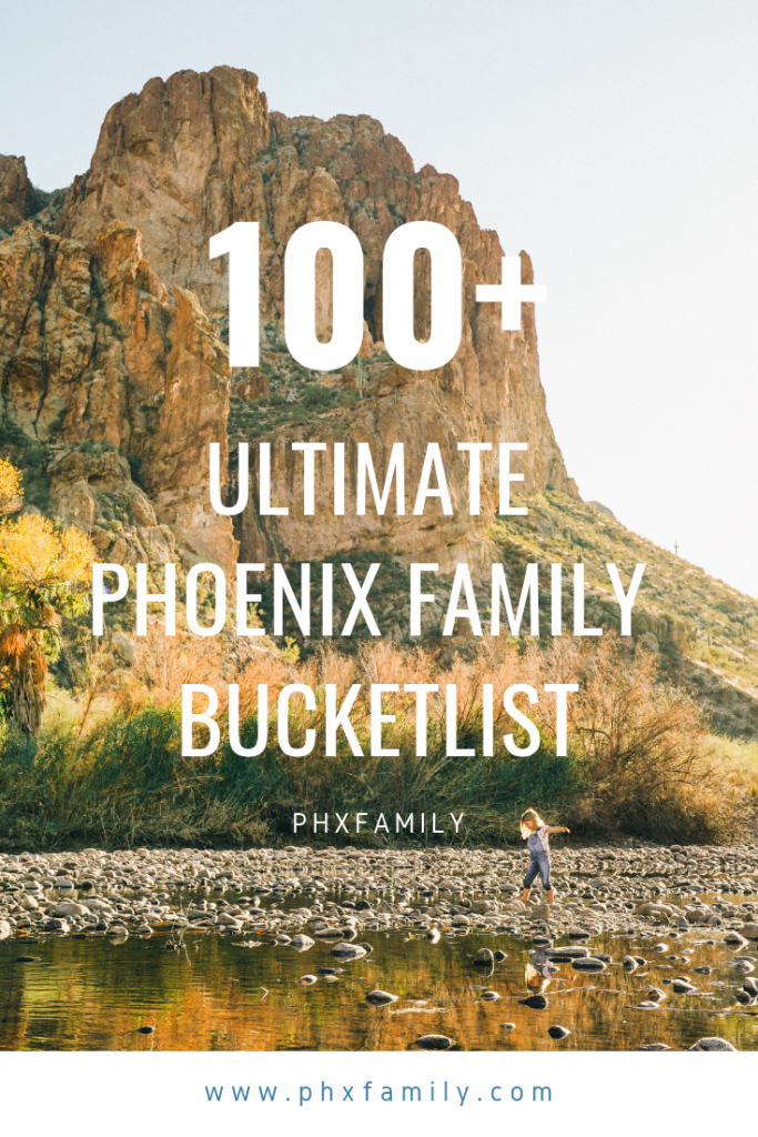 "Children wading in shallow river bed with large desert rock formation behind, text reads ""100+ Ultimate Phoenix Family Bucket List"""